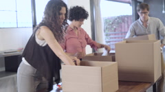 Business people unpacking boxes in office Stock Footage