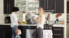 Lesbian mothers and son standing in kitchen Stock Footage