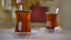 Stirring a glass of hot tea to dissolve the sugar I've just added Stock Footage