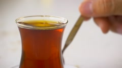 Slow Motion, Close up of Stirring a glass of hot tea to dissolve the sugar Stock Footage