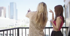 Young women point out things from balcony in Downtown Los Angeles 4K - stock footage