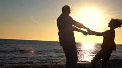 Young happy couple turning round on beach during sunset, super slow motion Stock Footage