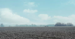 Cold field early in the morning with tractor pulling trailer in the distance. - stock footage