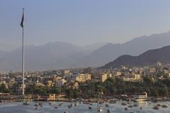 Elevated view of Aqaba seafront with huge Jordanian flag, boats and hazy - stock photo