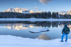 Hiker admires the snowy peaks and woods reflected in Lake Palu at dawn, Malenco - stock photo
