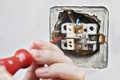 Change defective home electrical switch, dismantling of old device close-up. - stock photo