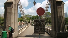 People walk by the historical Cavenagh bridge in Singapore. Stock Footage