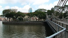 Person walks by the historical Cavenagh bridge in Singapore. Stock Footage
