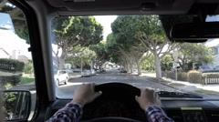 Person driving through suburbia. Point of view of driver Stock Footage