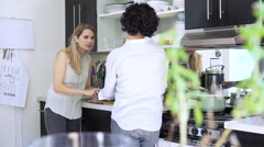 Lesbian couple cooking in kitchen Stock Footage