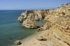 Overview of tourists on beach, sandstone cliffs and seastacks at Praia da Stock Photos
