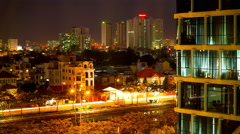 Zoom in view of streets and office buildings at night in Ho Chi Minh City Stock Footage