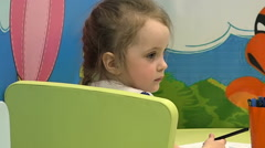 Little Blond Girl Draws in the Games Room, Glancing Around Stock Footage