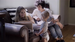 Lesbian mothers and son using laptop in living room Stock Footage