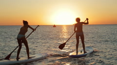 Group of Active Athletic People Engaged in Sup-Surfing on the Sea at Dusk Stock Footage