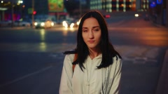 Young caucasian woman in city at night serious face portrait on blurred Stock Footage