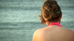 Contemplative woman meditating about life while looking at beach waves. Stock Footage