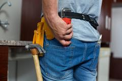 Rear view of man putting pipe wrench in pocket - stock photo