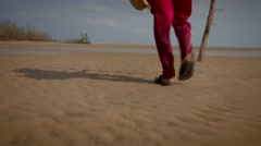 Man walking at a desert beach. Low angle shot of man holding a stick journeying - stock footage