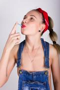 Beautiful young leggy blondy girl in a red bandana, denim overalls over his - stock photo