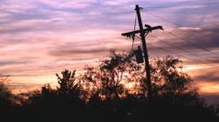 4K UHD dramatic shades of color post sunset behind tel pole trees time lapse Stock Footage