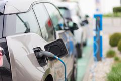 Electric Car in Charging Station. - stock photo