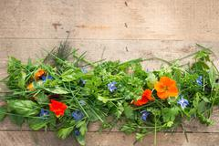 Variety of Herbs and Edible Flowers on Wooden Background Stock Photos