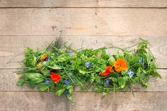 Heap of Edible Flowers and Herbs on Wooden Planks Stock Photos