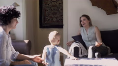 Lesbian mothers and son relaxing in living room Stock Footage