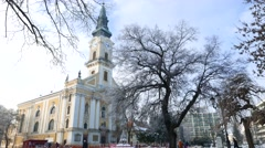 Static view of pedestrians passing by the Kecskemet Church in winter Stock Footage