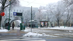Zoom out view of a tram stop in the centre of Szeged in winter Stock Footage
