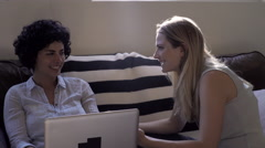 Lesbian couple using laptop on sofa Stock Footage