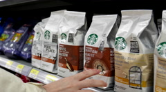Woman buying Starbucks breakfast blend and house coffee inside Walmart store - stock footage