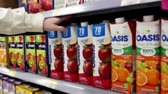 Woman buying Pomme apple juice inside Walmart store - stock footage