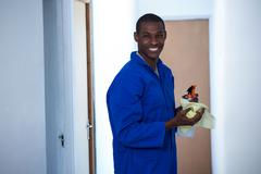 Happy handyman holding spraying insecticide and napkin Stock Photos