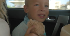 Boy with Plush Toy on the Car Back Seat Stock Footage