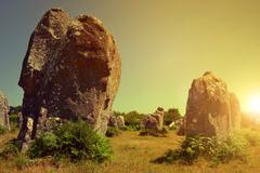 Megalithic monuments menhirs in Carnac at sunset - stock photo