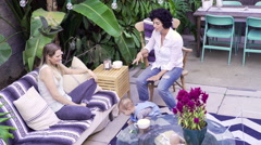 Lesbian mothers and son relaxing in backyard Stock Footage