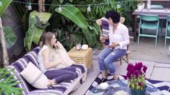 Lesbian couple talking in backyard Stock Footage