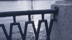 Slopping water (river) view through the iron fence - stock footage