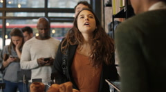4K Customer in cafe makes payment with smartphone while queue of customers wait  Stock Footage