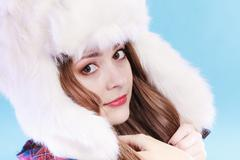 Young woman in winter clothing fur cap - stock photo