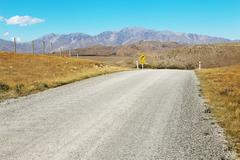 Empty rural road near mountains in new zealand Kuvituskuvat