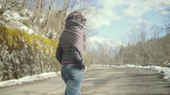 Romantic brunette woman walking along the road, looking around Stock Footage