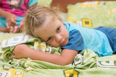 Little girl sitting on a double bed and frightened looks into the distance - stock photo