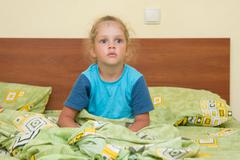 Little girl sitting on a double bed and frightened looks into the distance Stock Photos