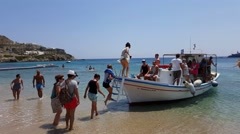 Mykonos, Greece - Tourists embarking in a water taxi at Paradise beach. Stock Footage