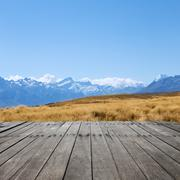 Empty wood floor with pasture near snow mountains in blue sky Stock Photos
