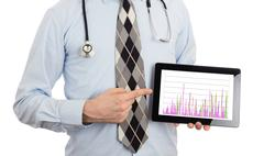 Doctor holding tablet - Graph - stock photo
