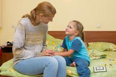 Mom wants to sleep good night to her daughter sitting on the bed in the room - stock photo